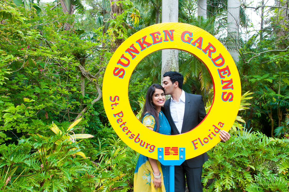 Indian couple posing by the Sunken Gardens, St. Petersburg, Florida sign during their Florida Indian Engagement Photography photo-shoot