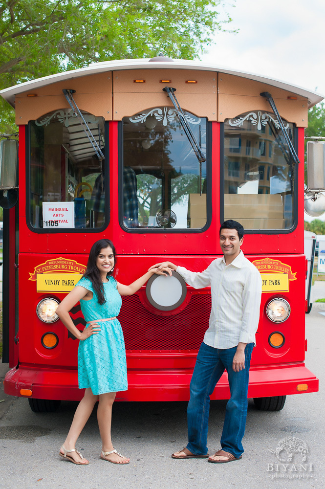 Engaged Indian Couple posing in-front of a red bus in Downtown Tampa for their Indian Engagement photos