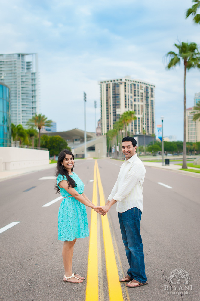 Indian couple holding hands in the middle of the road in Tampa Bay, Florida - right outside the Dali Museum