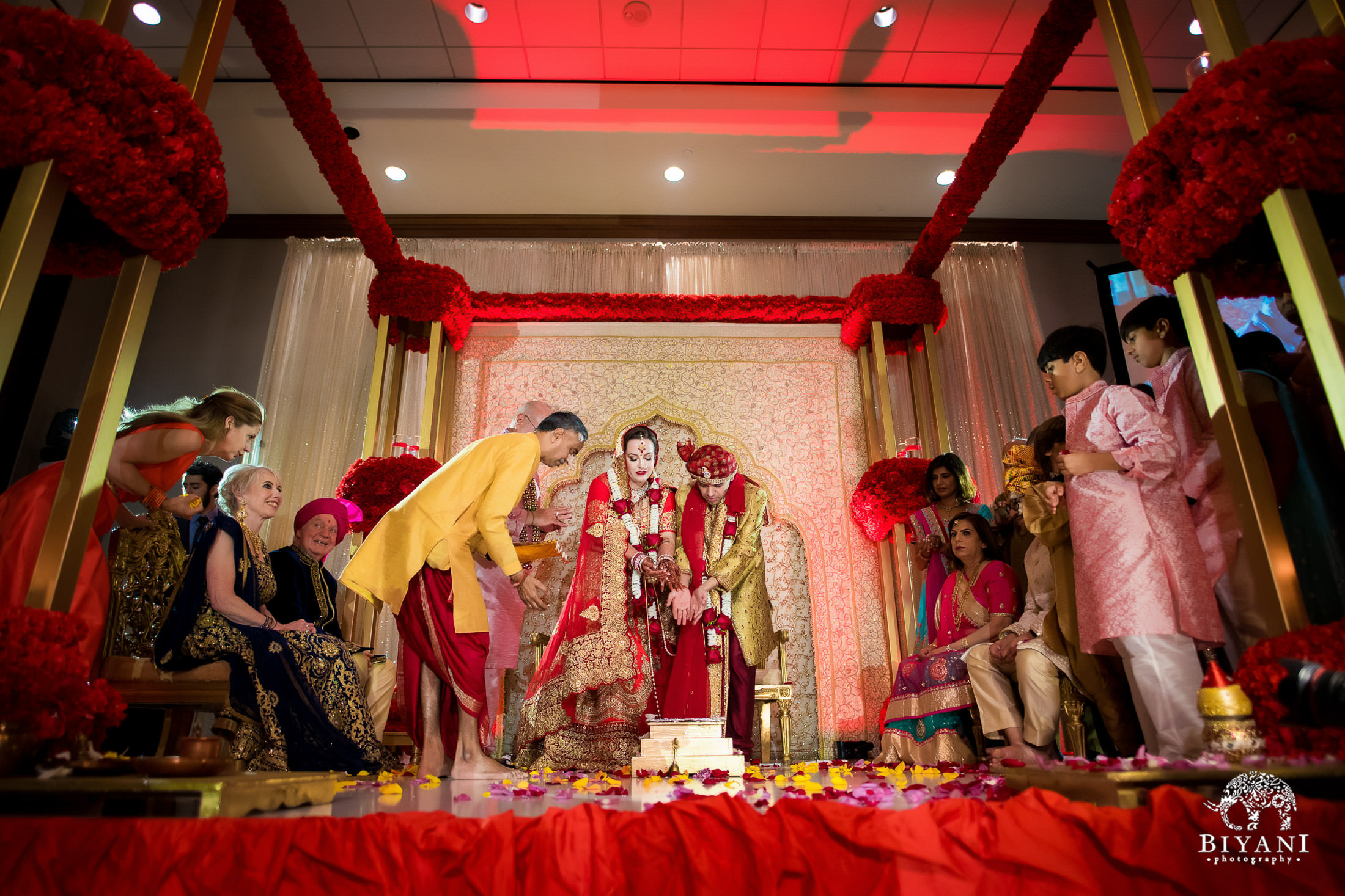 Bride and groom throw offerings into the fire