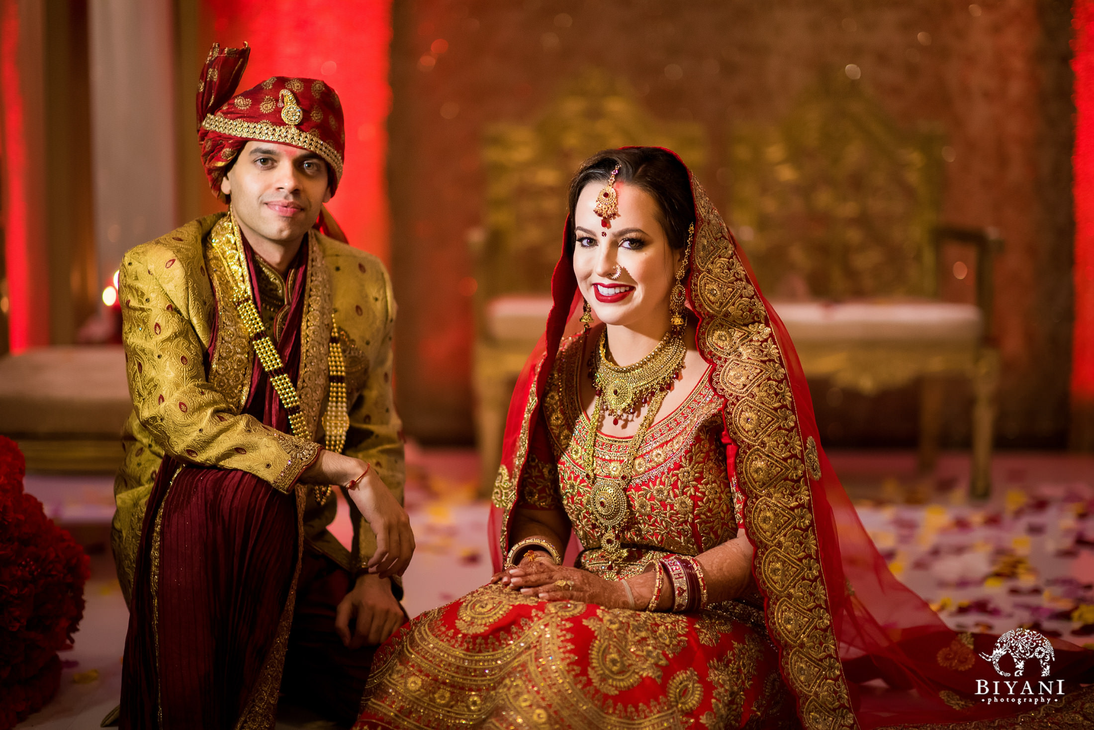 Bride and groom pose together in ceremony outfits