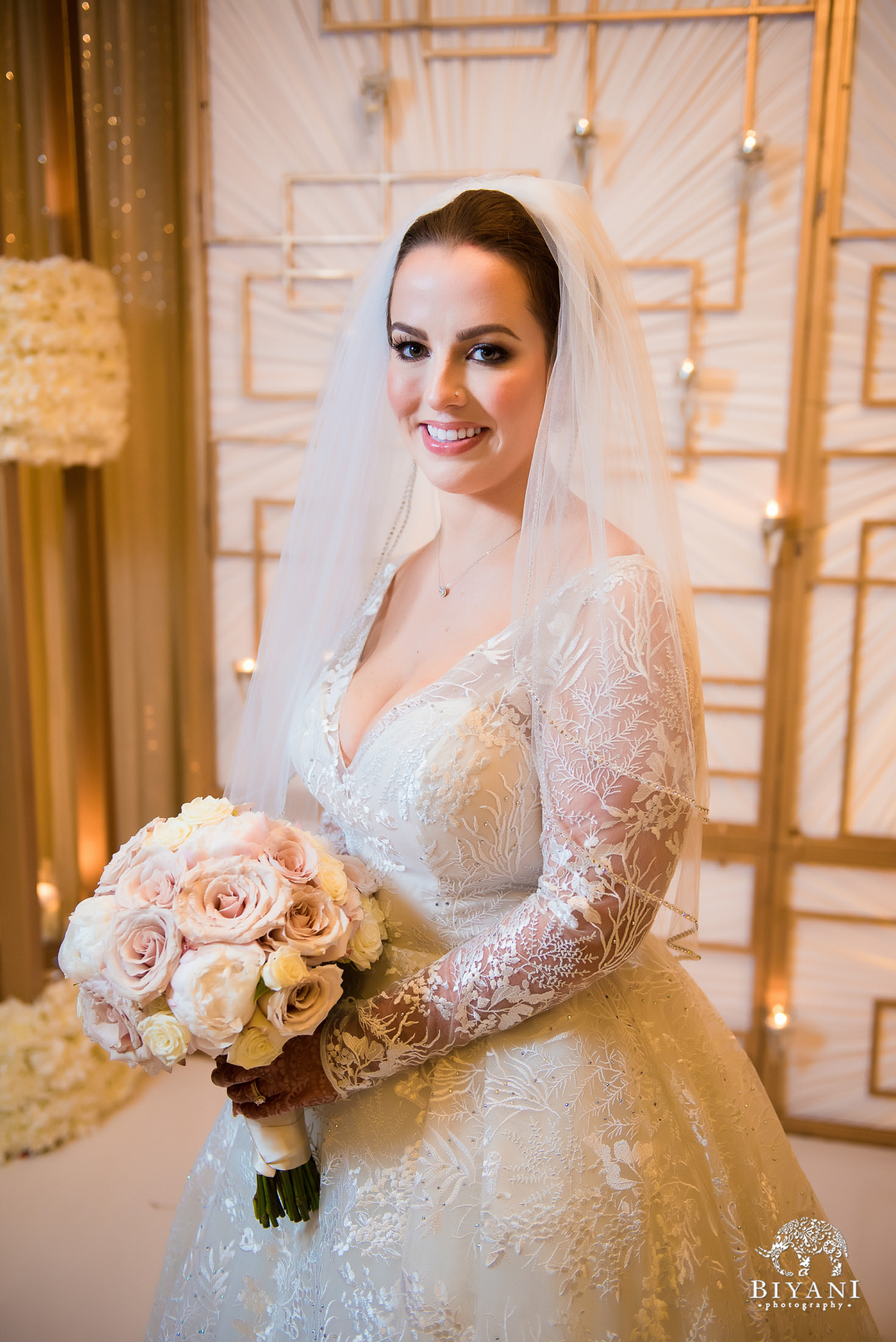 Bride poses with bouquet of flowers in American ceremony outfit