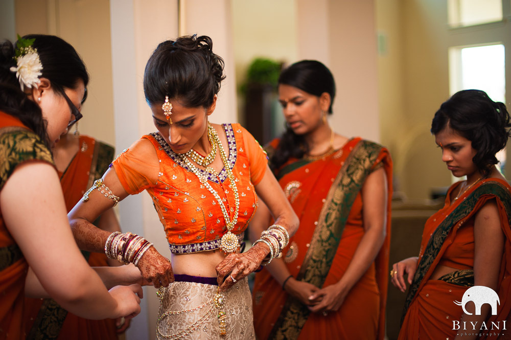 Bridesmaids helping bride put on her Indian Wedding Dress