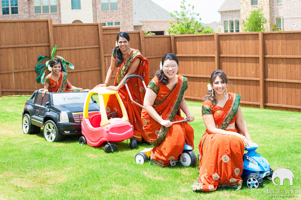 Bridesmaids in goofy kid/toy cars in the yard