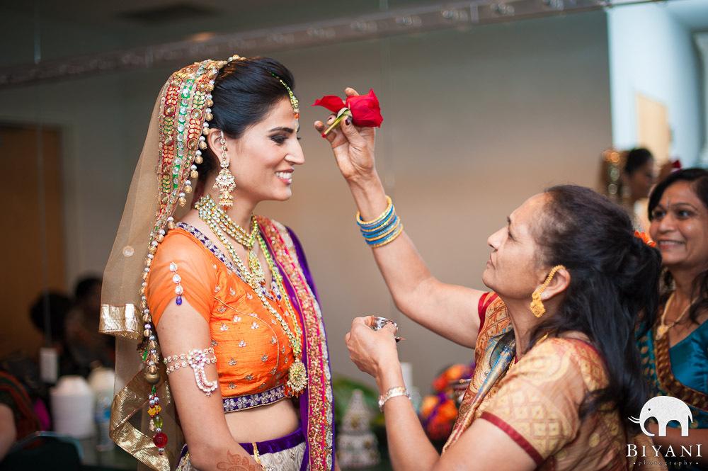 Bride getting a teeka on her forehead - auspicious red dot