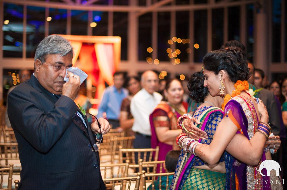 teary eyed bride hugging her mom, dad wiping tears - Vidaai