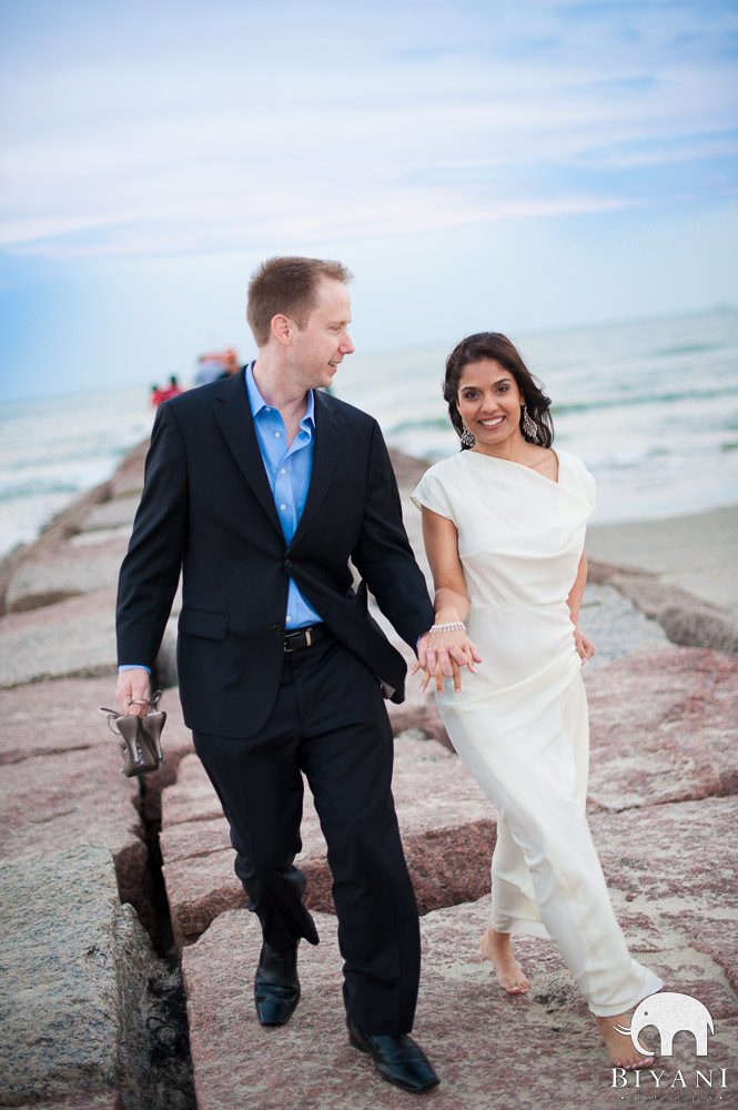 Engaged Indian couple walking on pier
