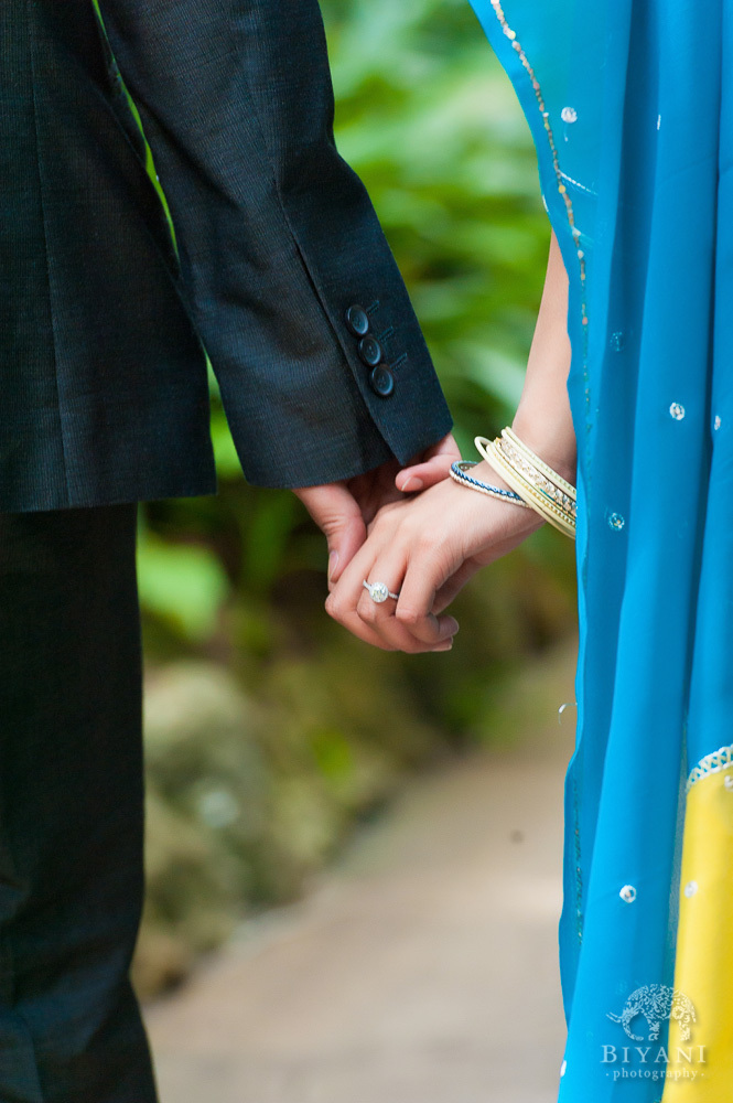 Engaged Indian couple holding hands with fiance's Engagement Ring showing at Sunken Gardens in St. Petersburg Florida
