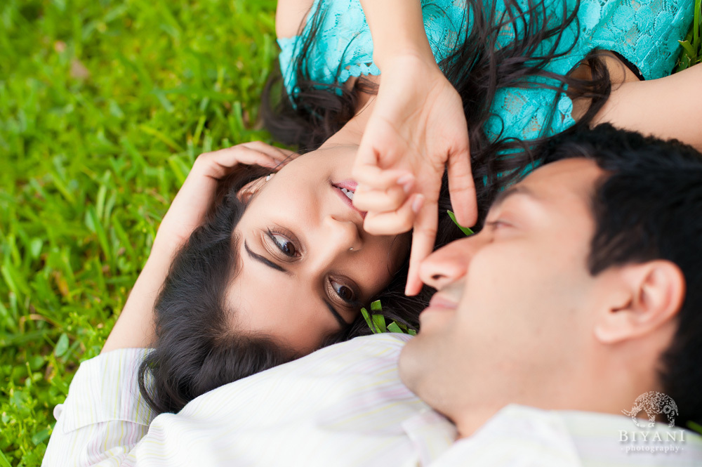 Indian Couple laying in the grass and holding each other at the Tampa Beach in Florida during their Indian Engagement Photography session