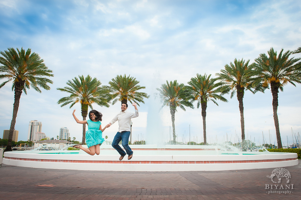 Engaged Indian Couple jumping with joy in front of palm trees and a fountain, across the street from the Dali Museum in Tampa, Florida