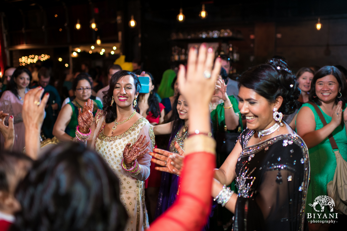 Indian bride dancing with sister-in-law and friends