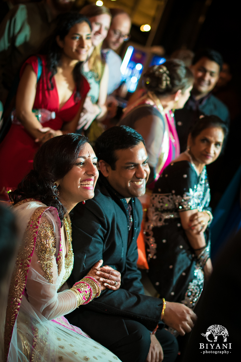 Couple smiling and laughing during Sangeet toasts from friends