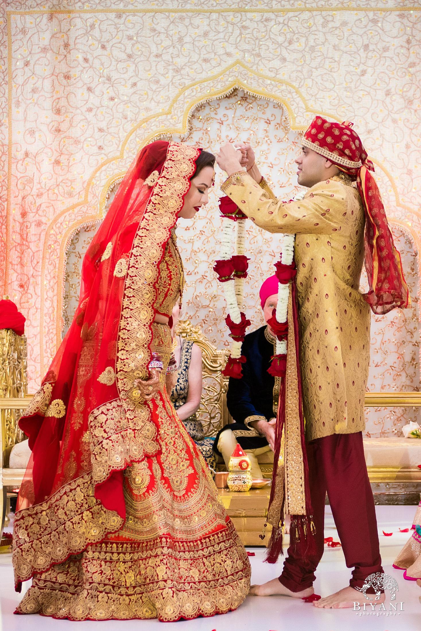 Groom adorns bride with ceremony bands