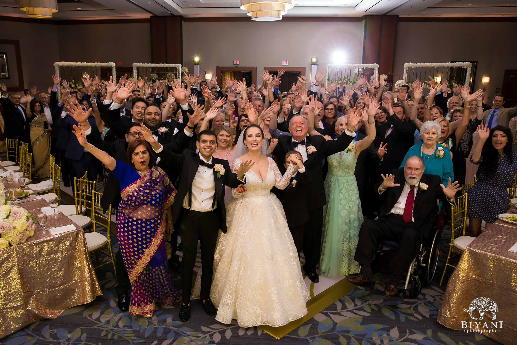 Bride and groom join their families for large family photo
