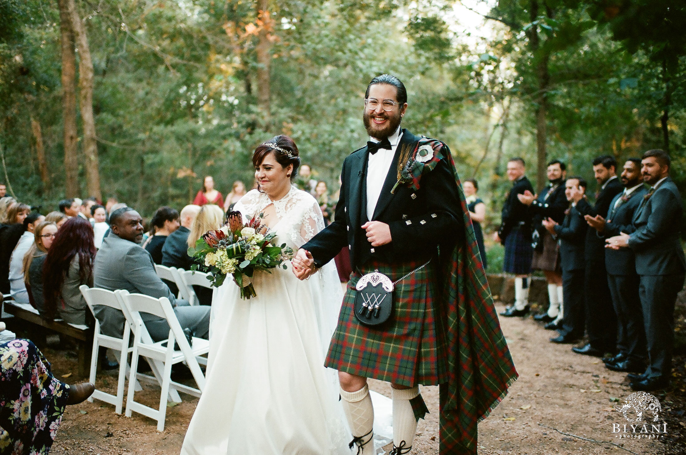 Groom in a kilt and bride in a wedding dress departing their wedding ceremony in a forest - Houston Arboretum