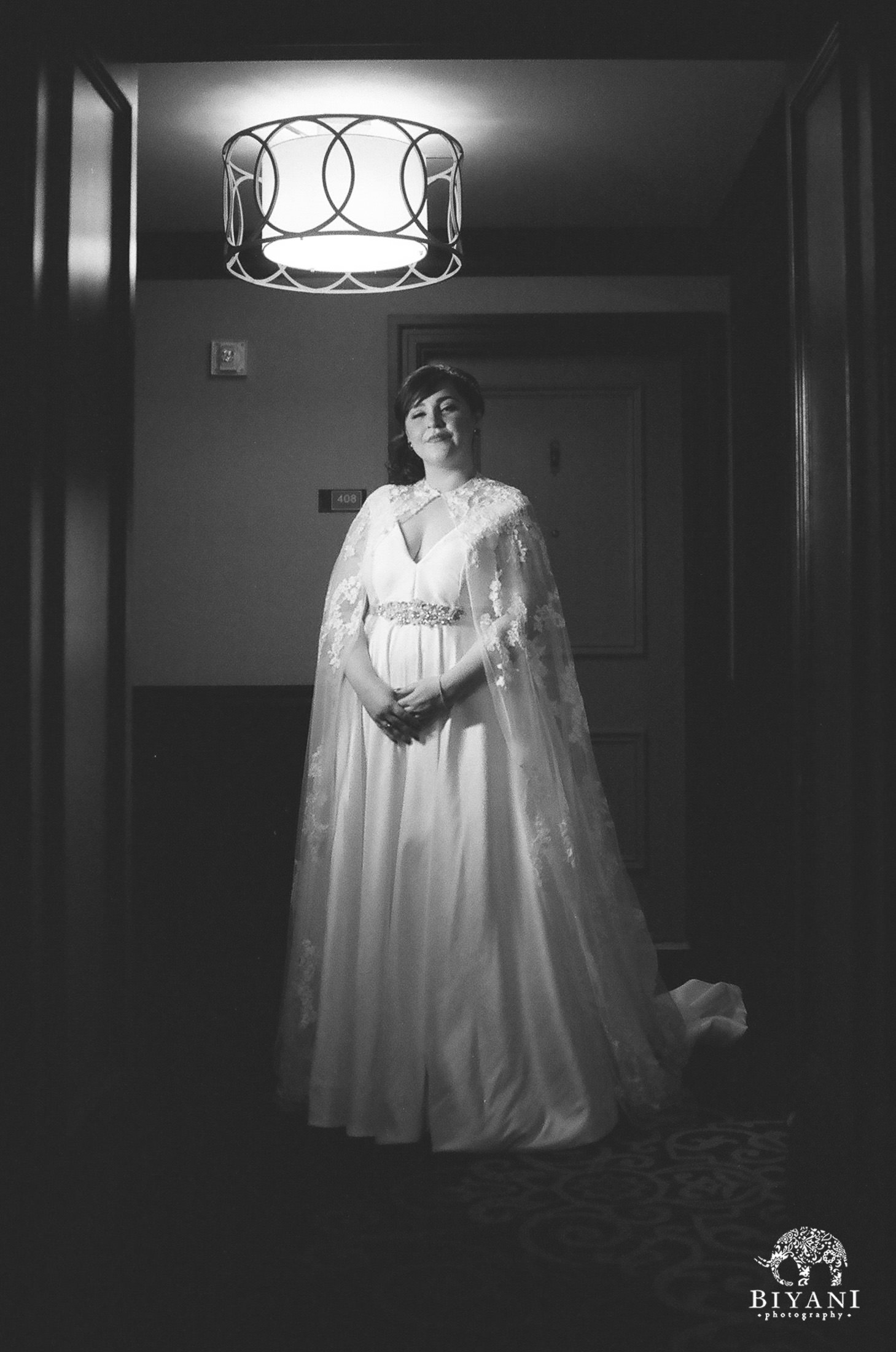 Bride wearing a cape along with her wedding gown