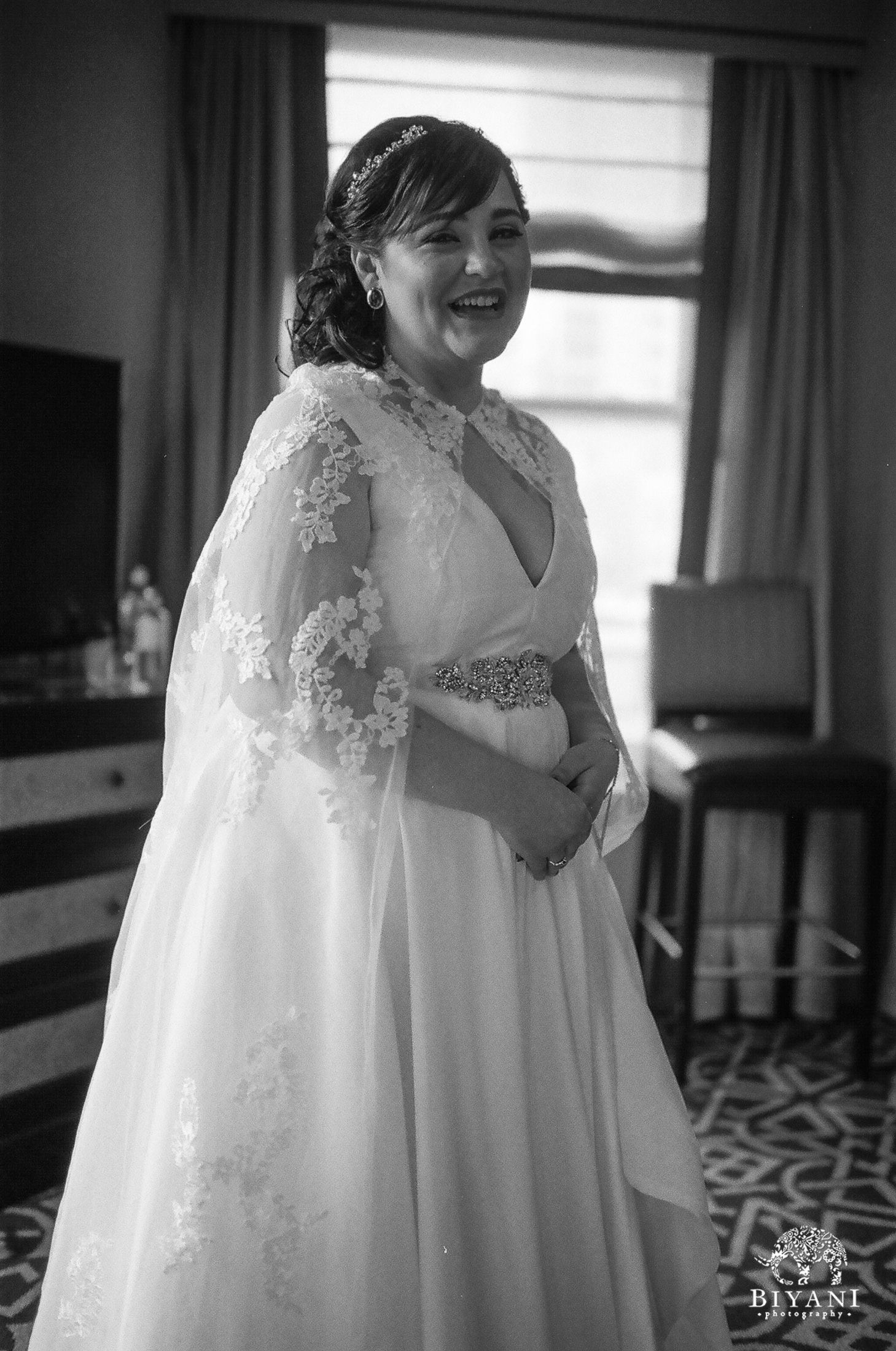 Bride smiling & laughing while getting dressed