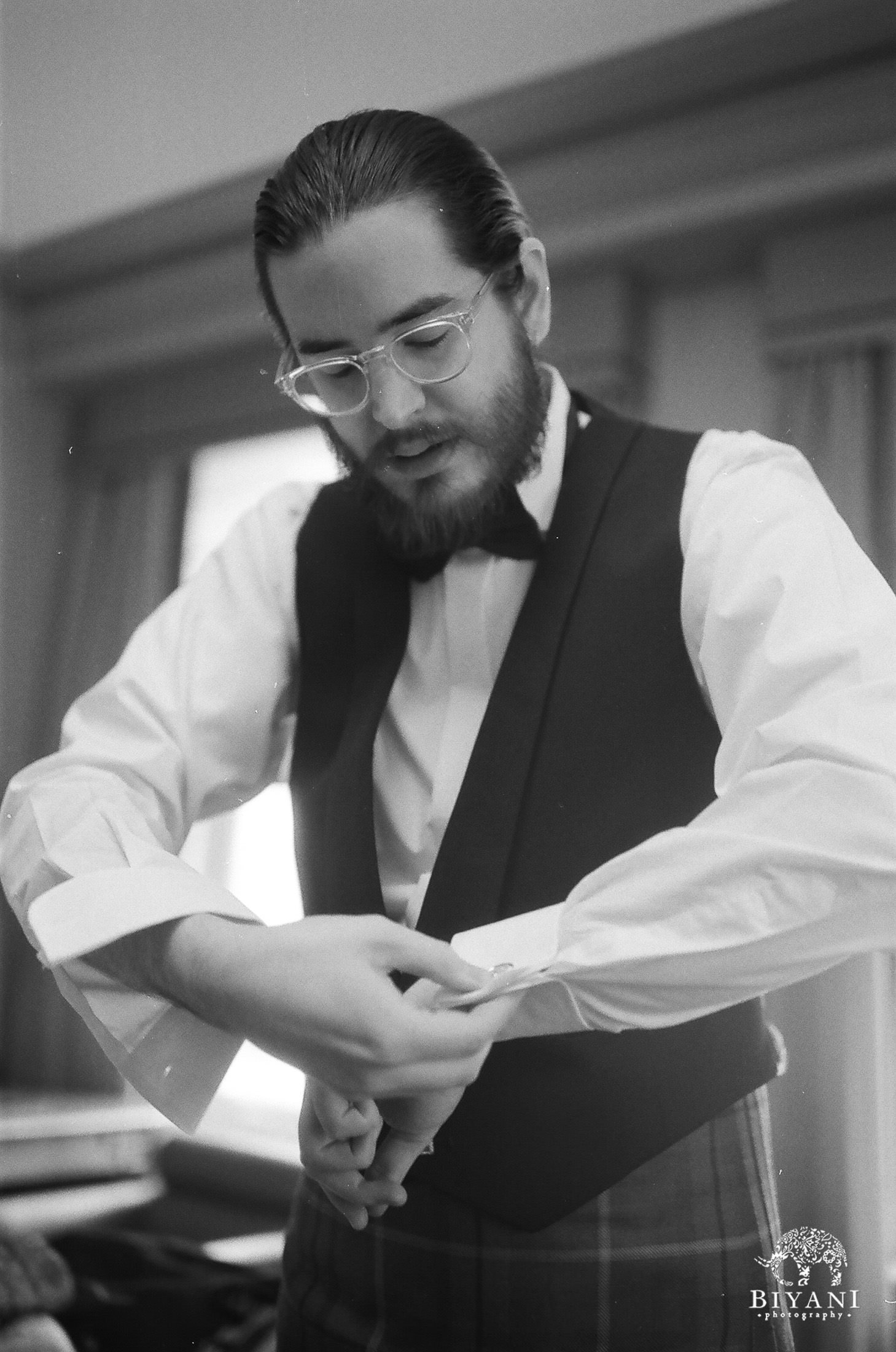 Groom putting on his cufflinks