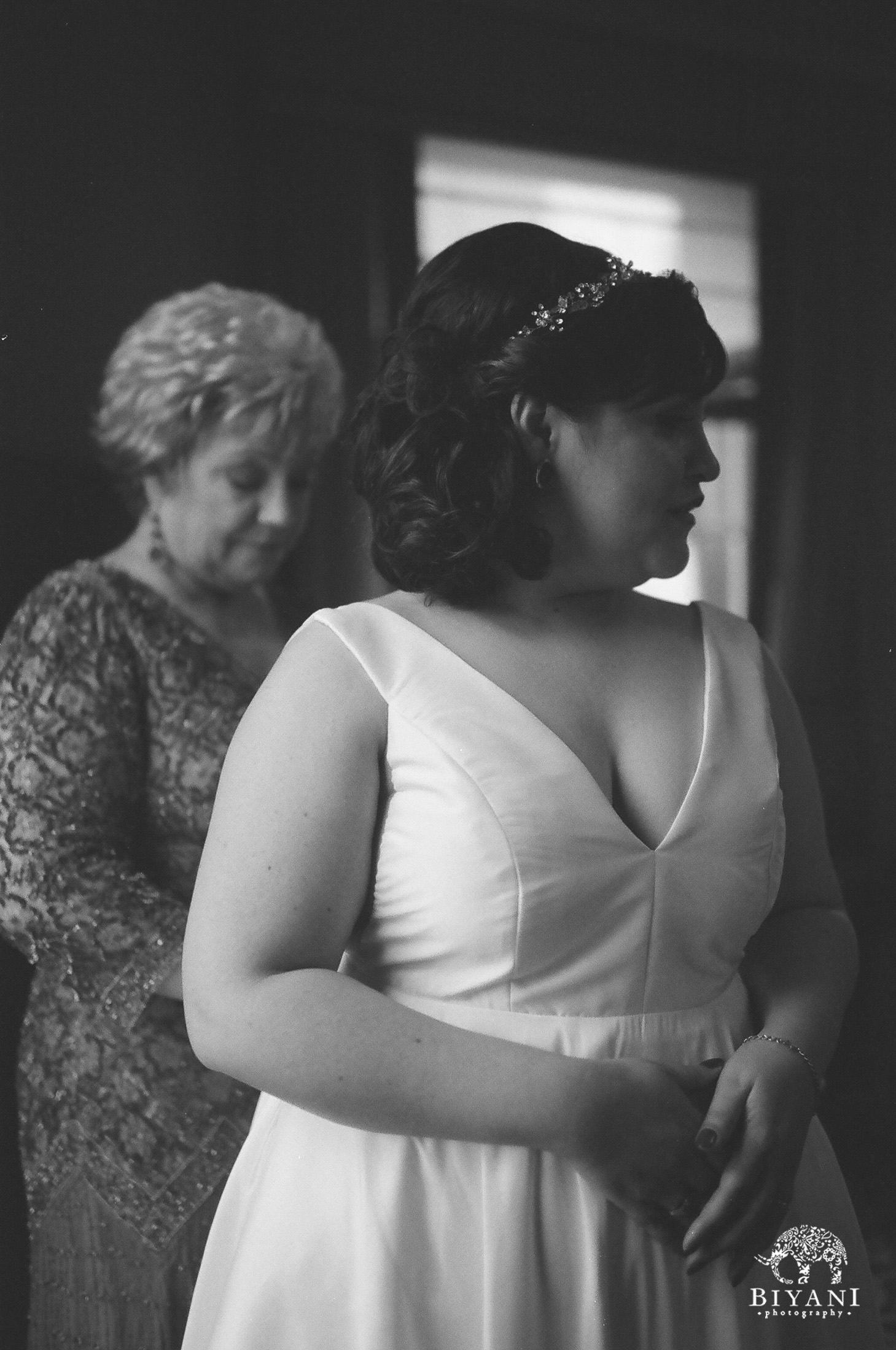 Bride's mother helping bride get dressed