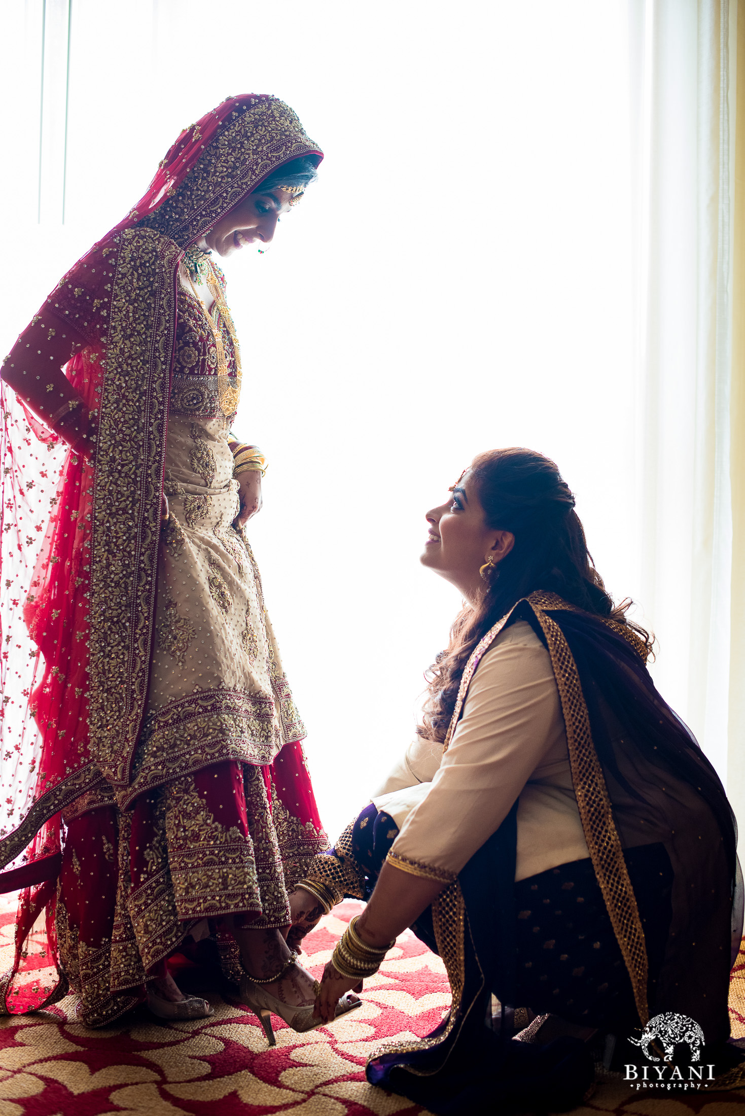 Indian bride and her sister helping her get ready before her wedding ceremony