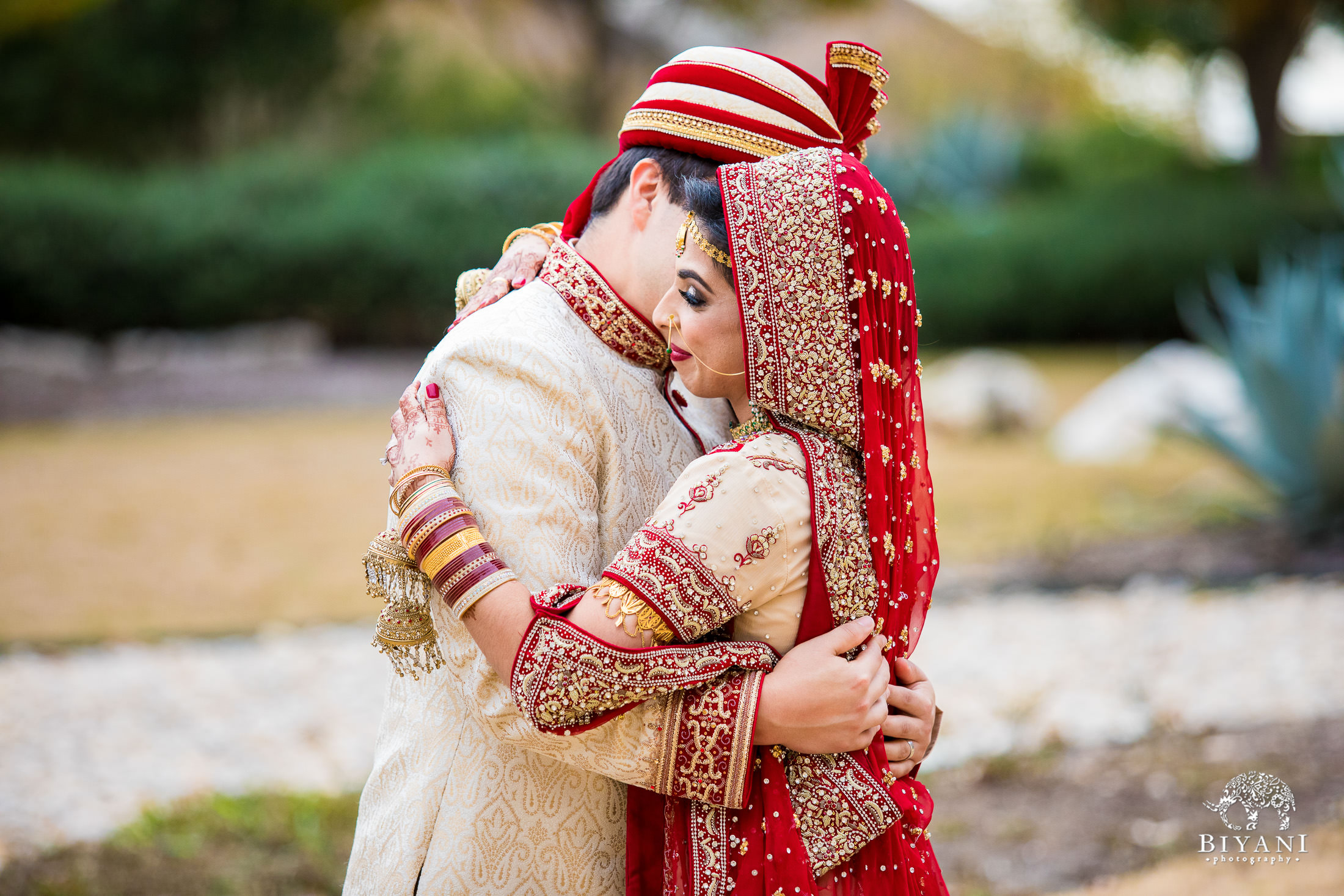 Indian Fusion Bride and Groom hugging after their first look outdoors