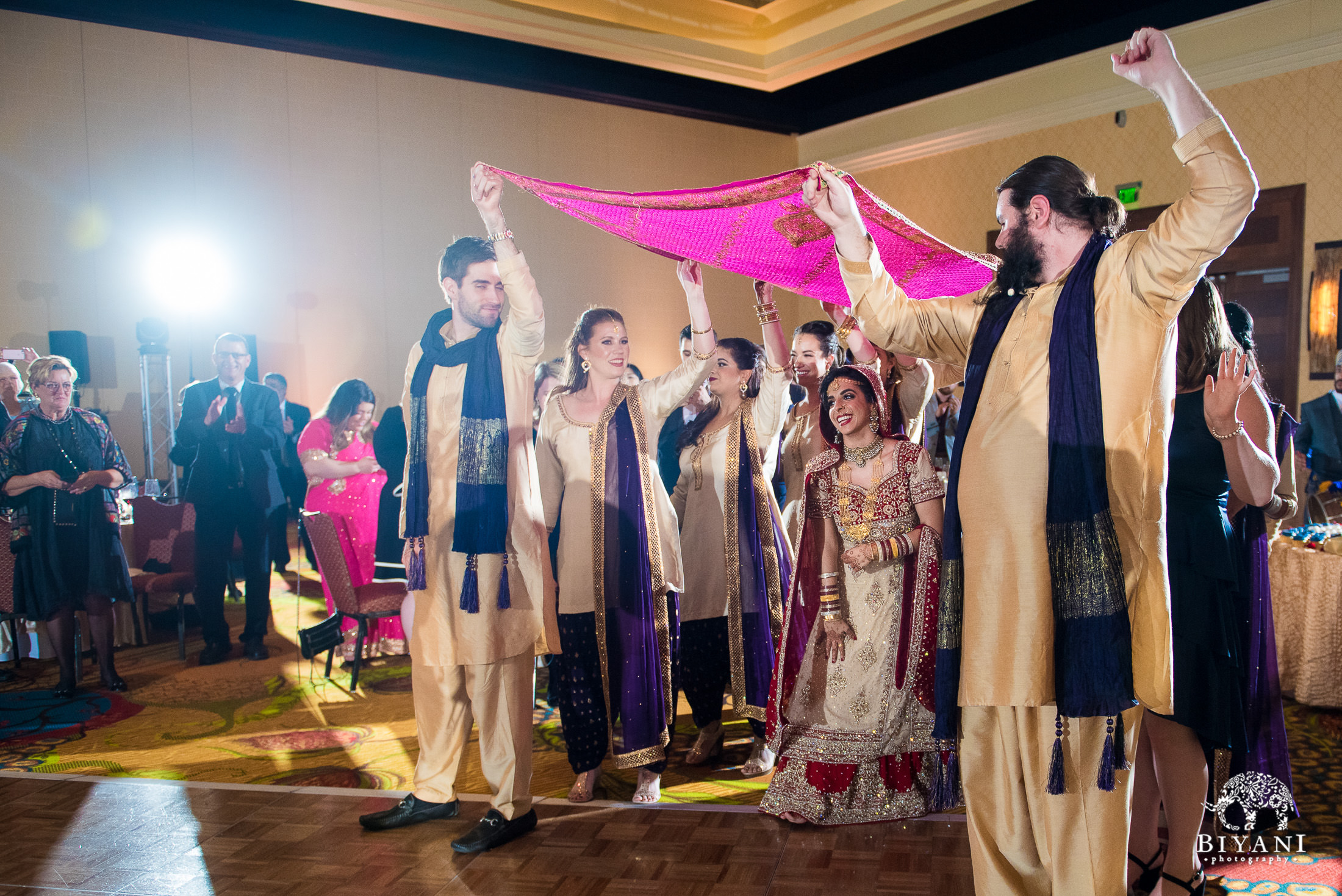 Indian bride entering reception party with groomsmen and bridesmaids