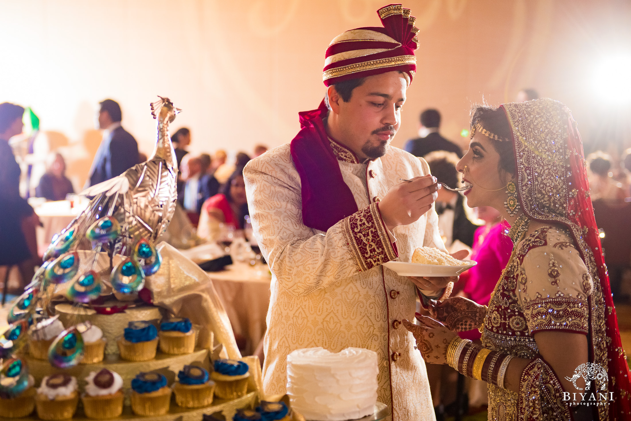Groom feeds bride cake during Indian Fusion wedding reception party
