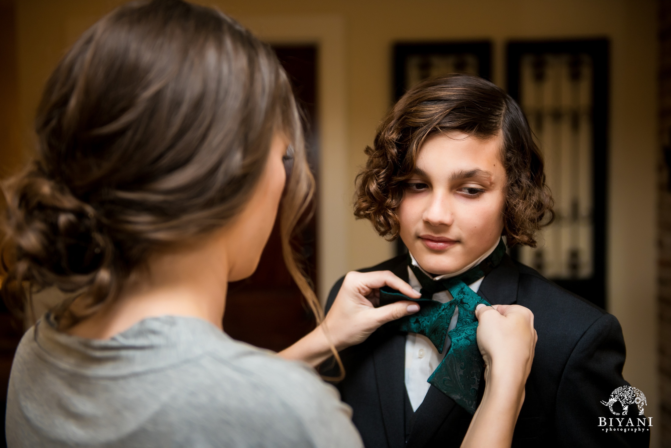 Bride tying the ring bearer's bow tie