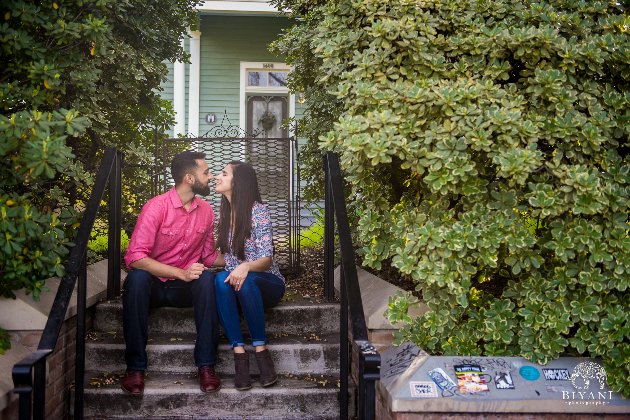 Indian couple sitting on steps posing for an engagement photo shoot in south Congress Austin, TX