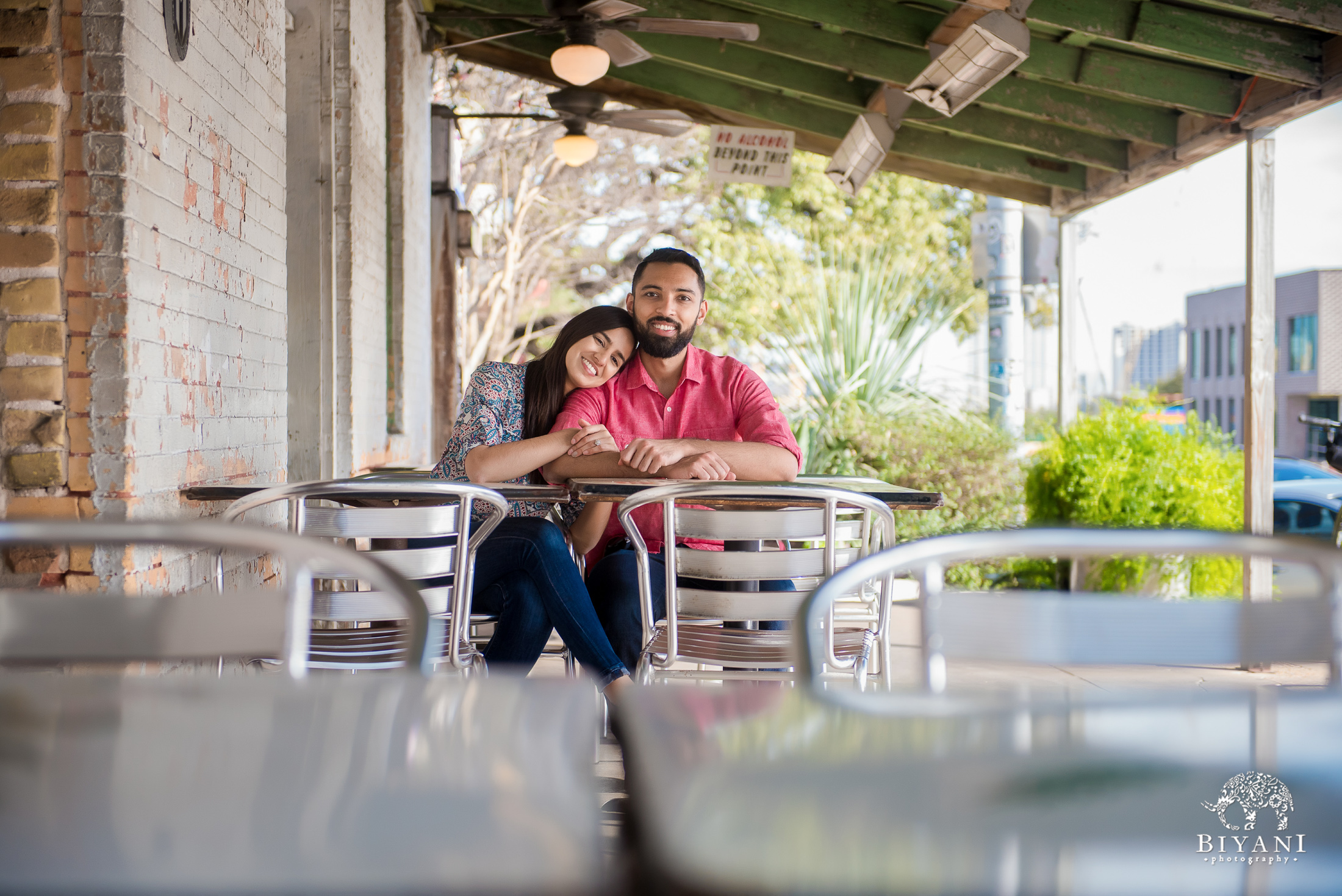 Indian couple sitting down at a restaurant table during their engagement photo shoot in South Congress Austin, Tx. on a sunny day