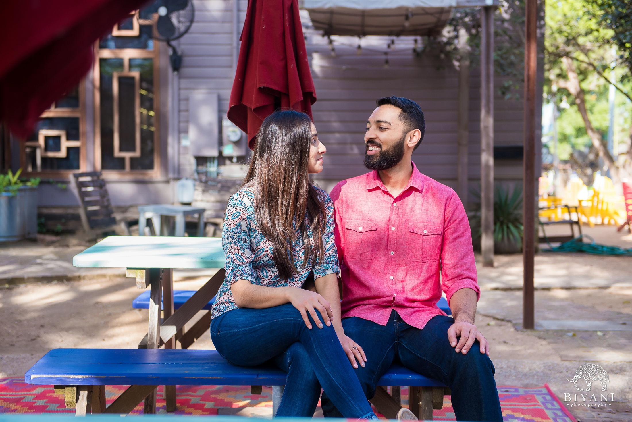 Indian couple sitting down on a picnic bench under a canopy during their engagement photo shoot in South Congress Austin, Tx. on a sunny day