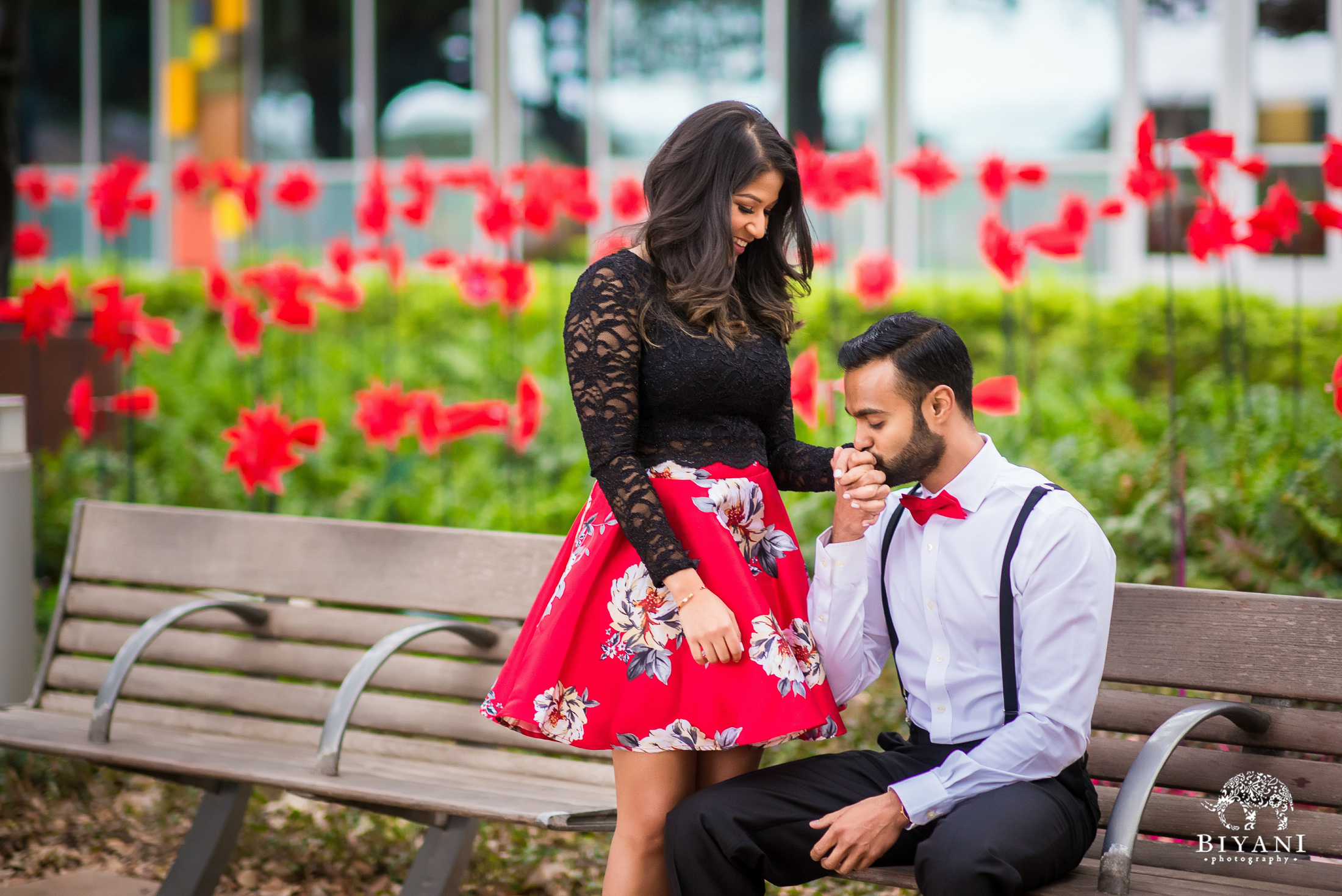 groom kisses his soon to be bride on the hand in a park with red flowers in the back