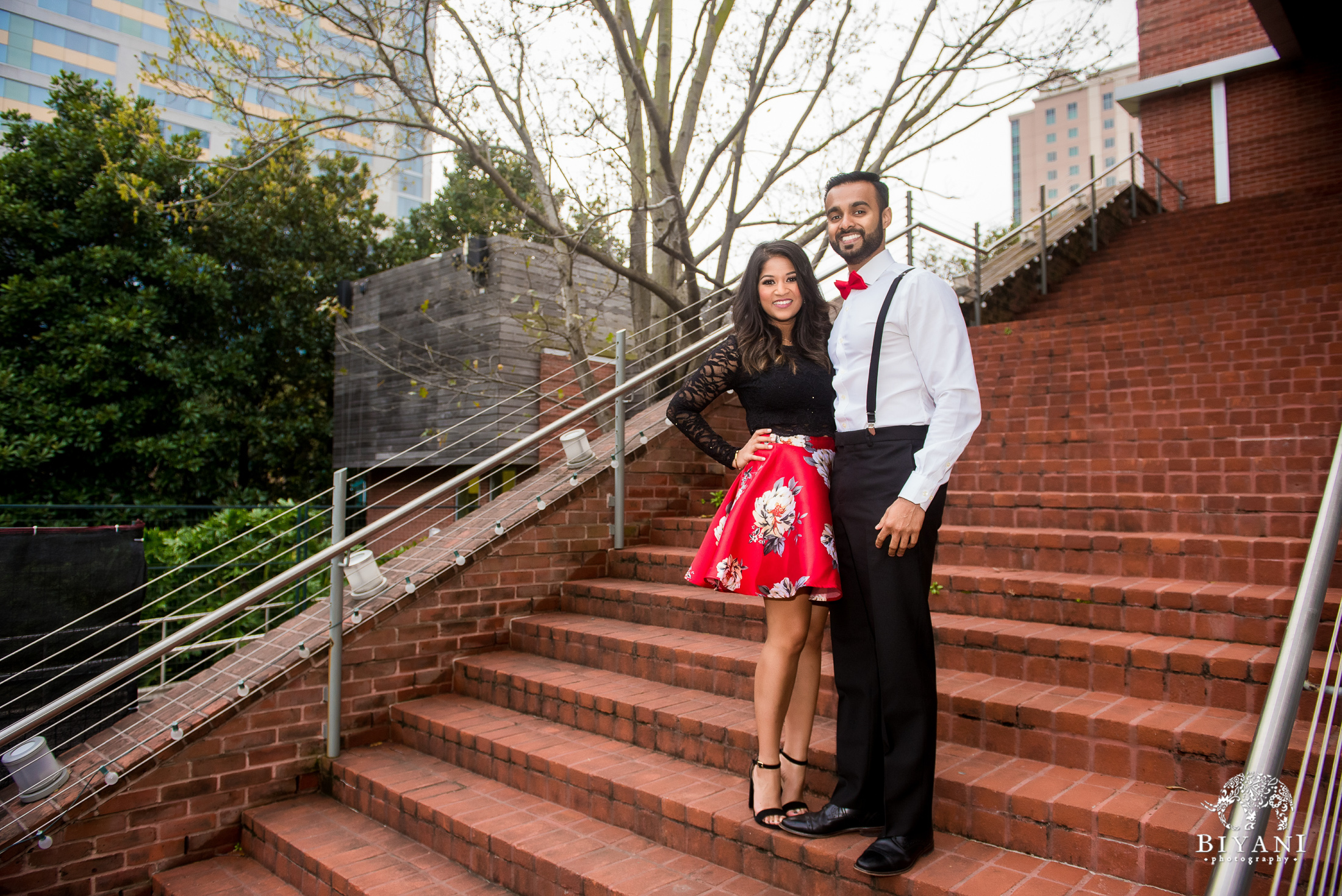 Sri Lankan couple standing on staircase during an engagement photo shoot in Houston, Tx. Discovery Green Park