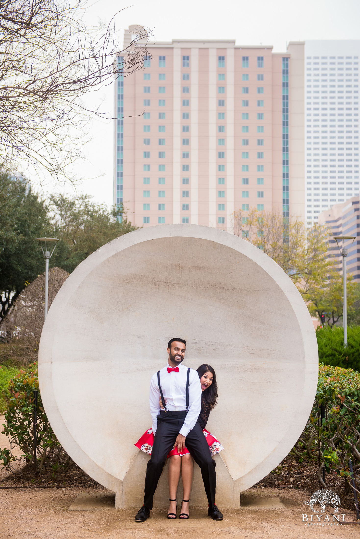 couple poses at the Listening Vessels and makes funny faces in Houston, Tx. Discovery Green Park