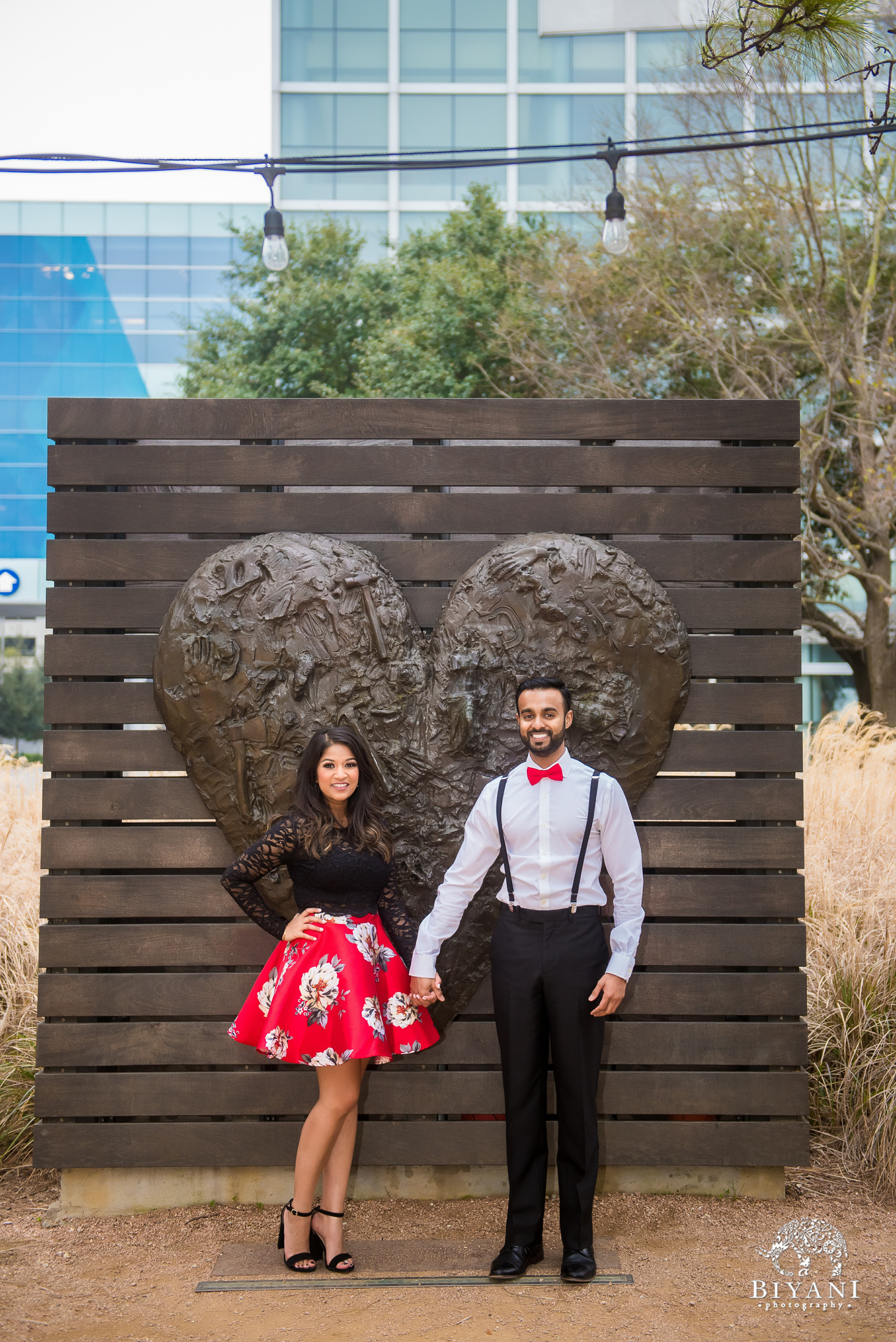 couple holds hand in front of a heart statue