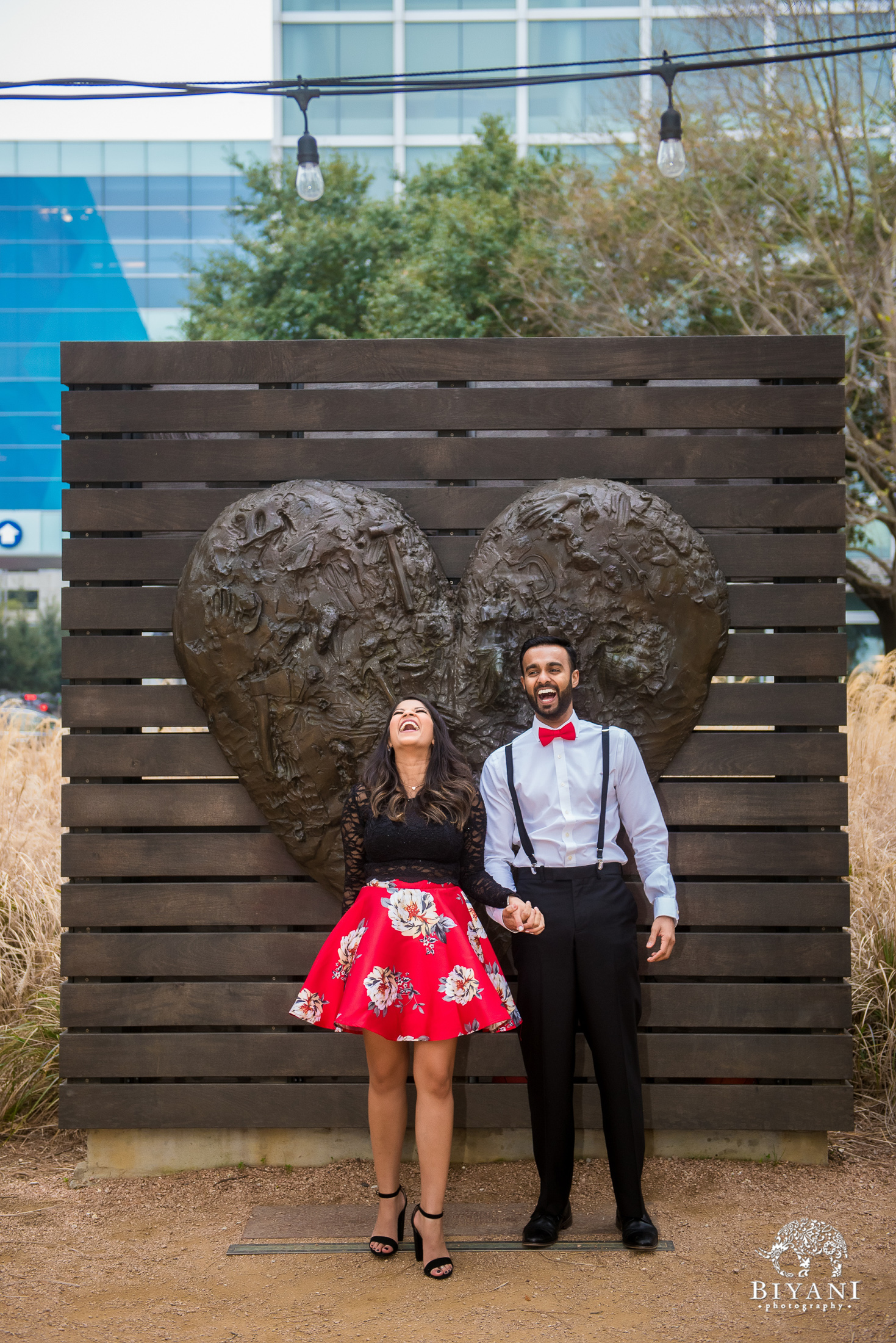 couple holds hand in front of a heart statue and makes silly poses