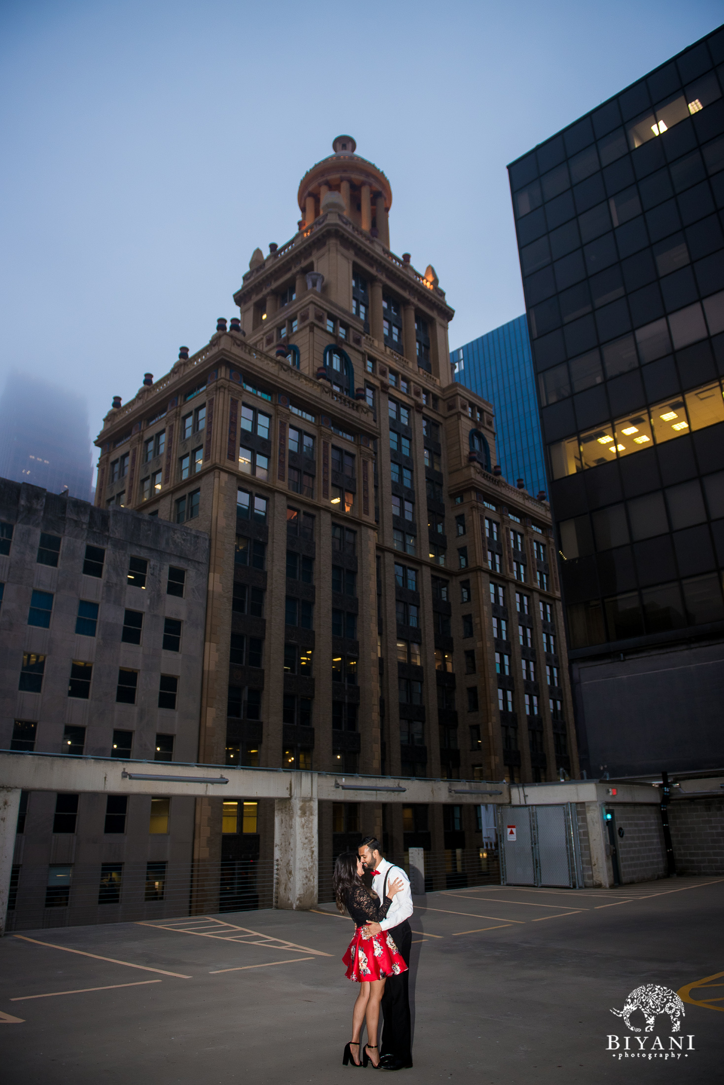 bride and groom hug during engagement shoot in front of Houston buildings