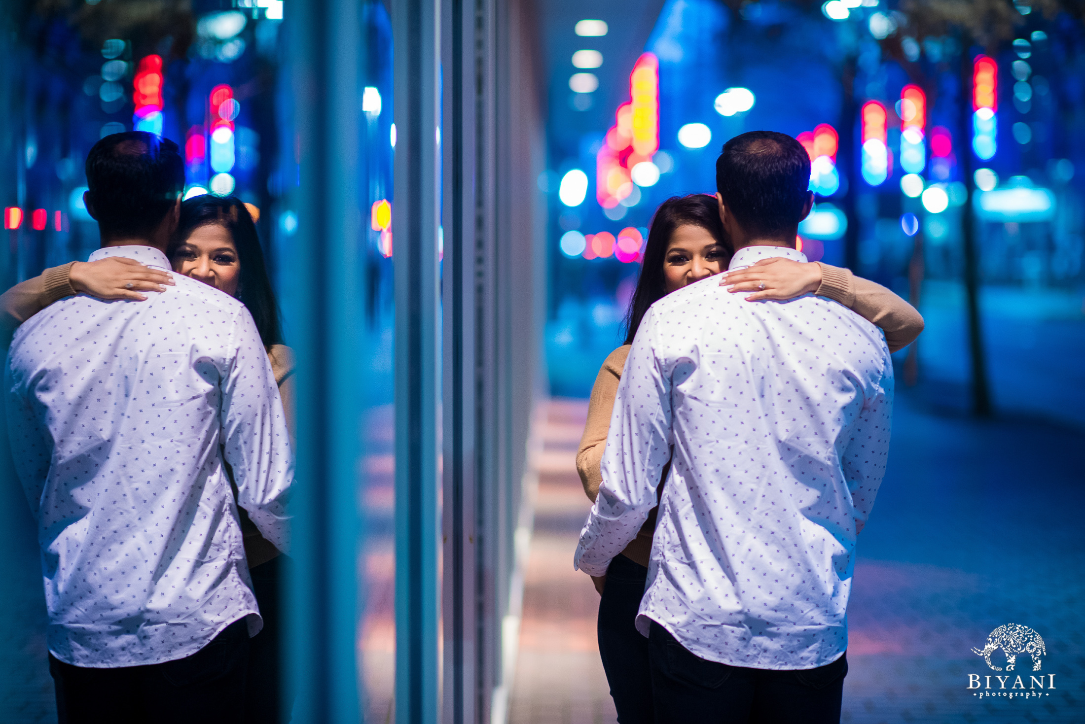 couple holding each other during the night time with bright city lights surrounding them