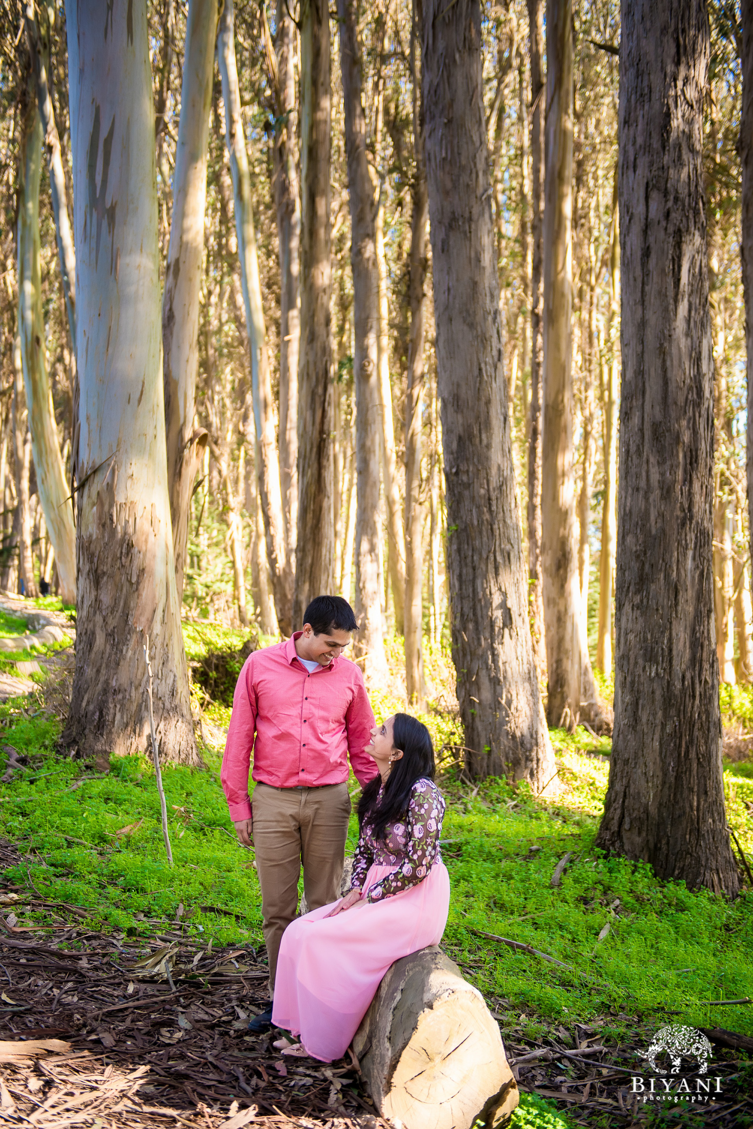 couple in a forest in San Francisco during engagement photo shoot on a sunny day