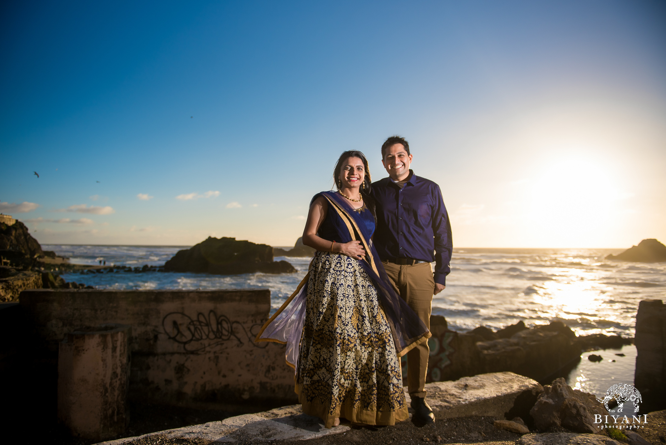 San Francisco Indian Engagement photo shoot with couple posing in front of the ocean front during sunset dressed in traditional Indian dress