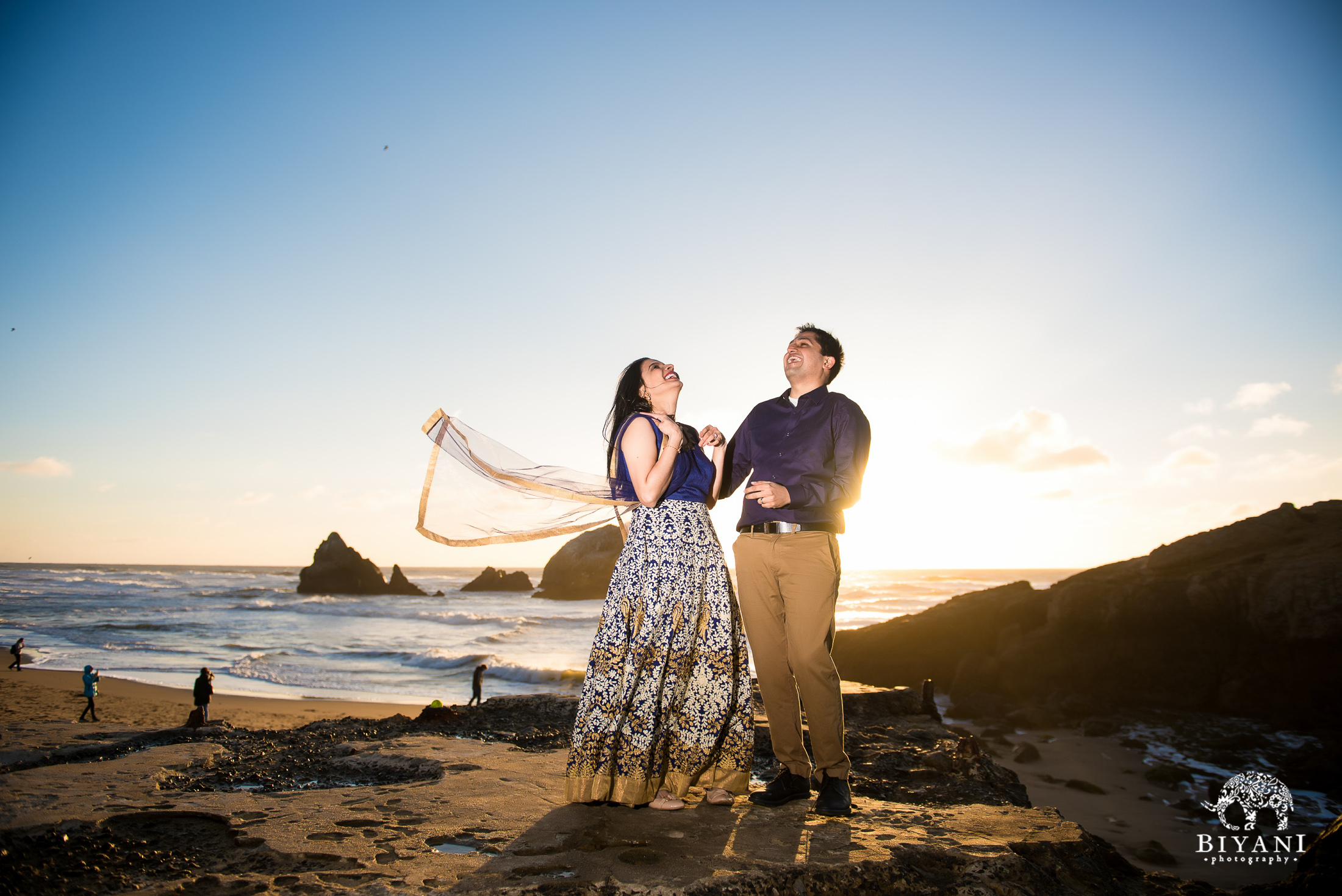 couple standing in front of the beach during engagement photo shoot at sunset in San Francisco