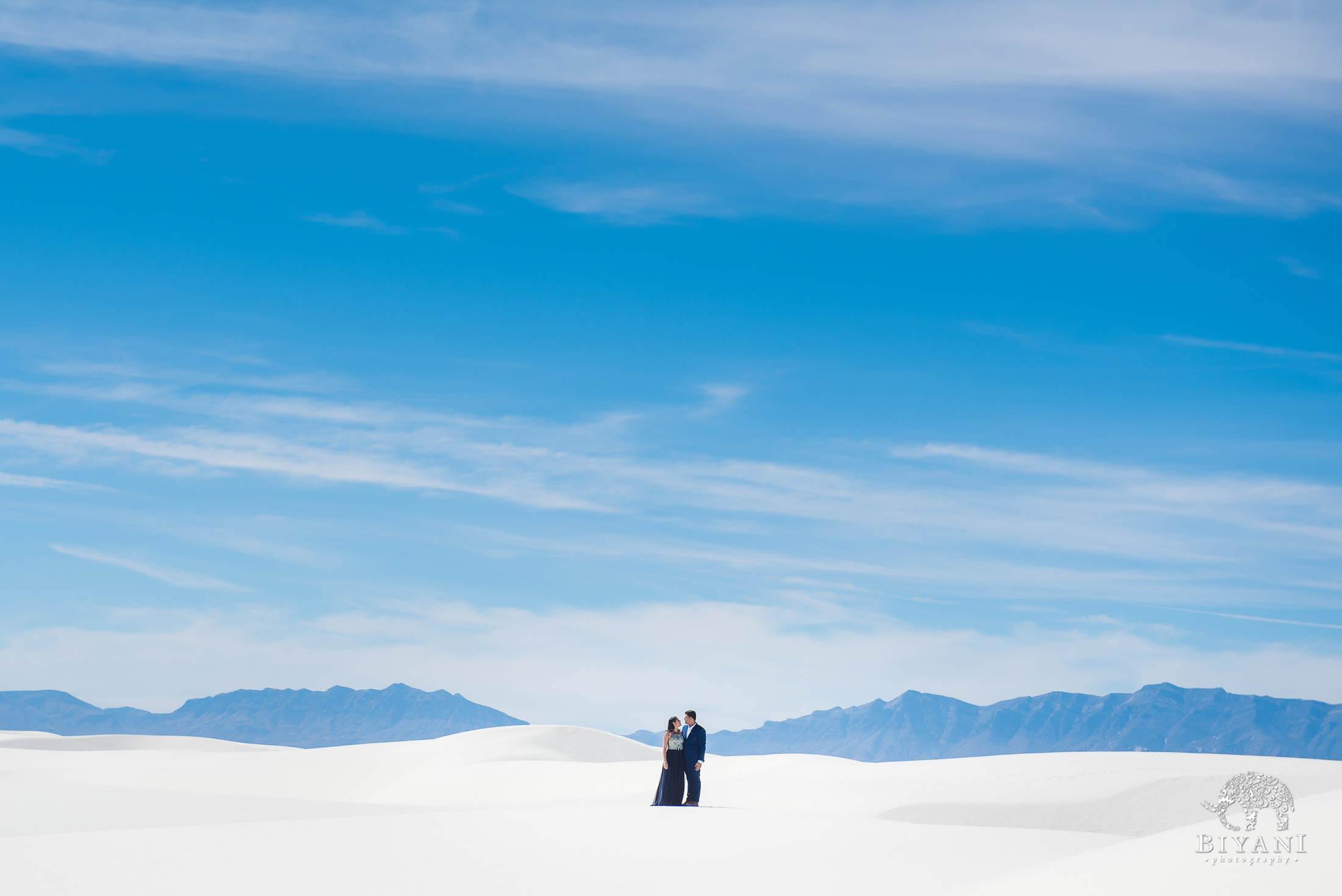 Couple together at the white sands national monument photographed from a distance