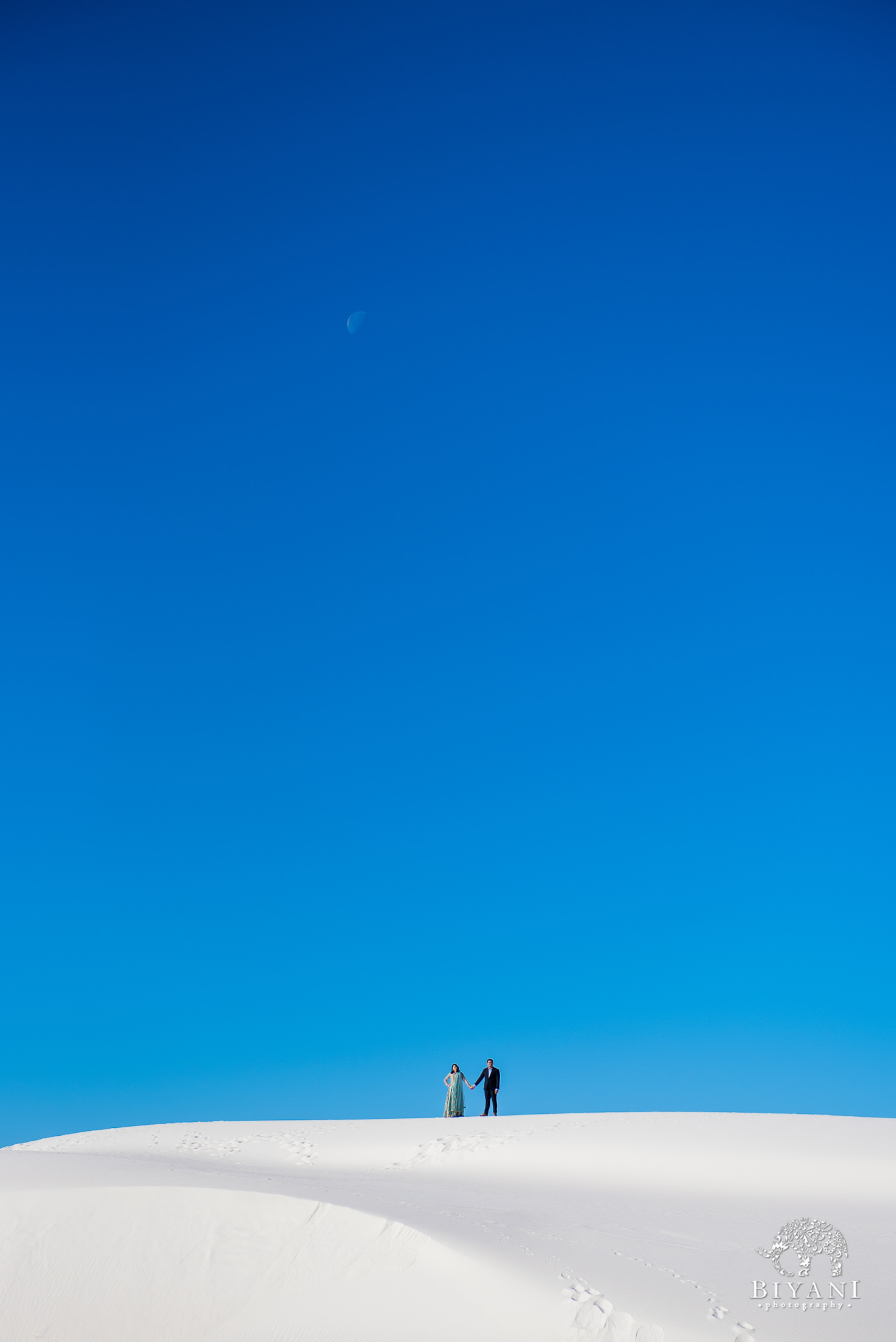 Couple on top of sand dune at White Sands National Monument park in New Mexico