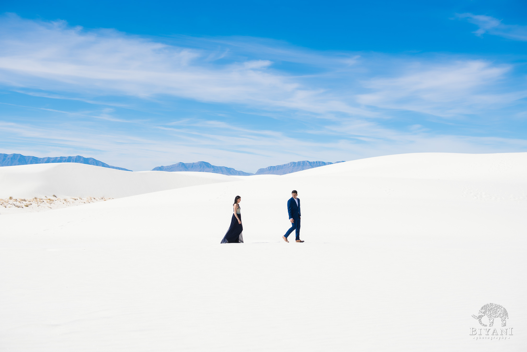 couple walking across sand dunes at White Sands with groom a few steps ahead