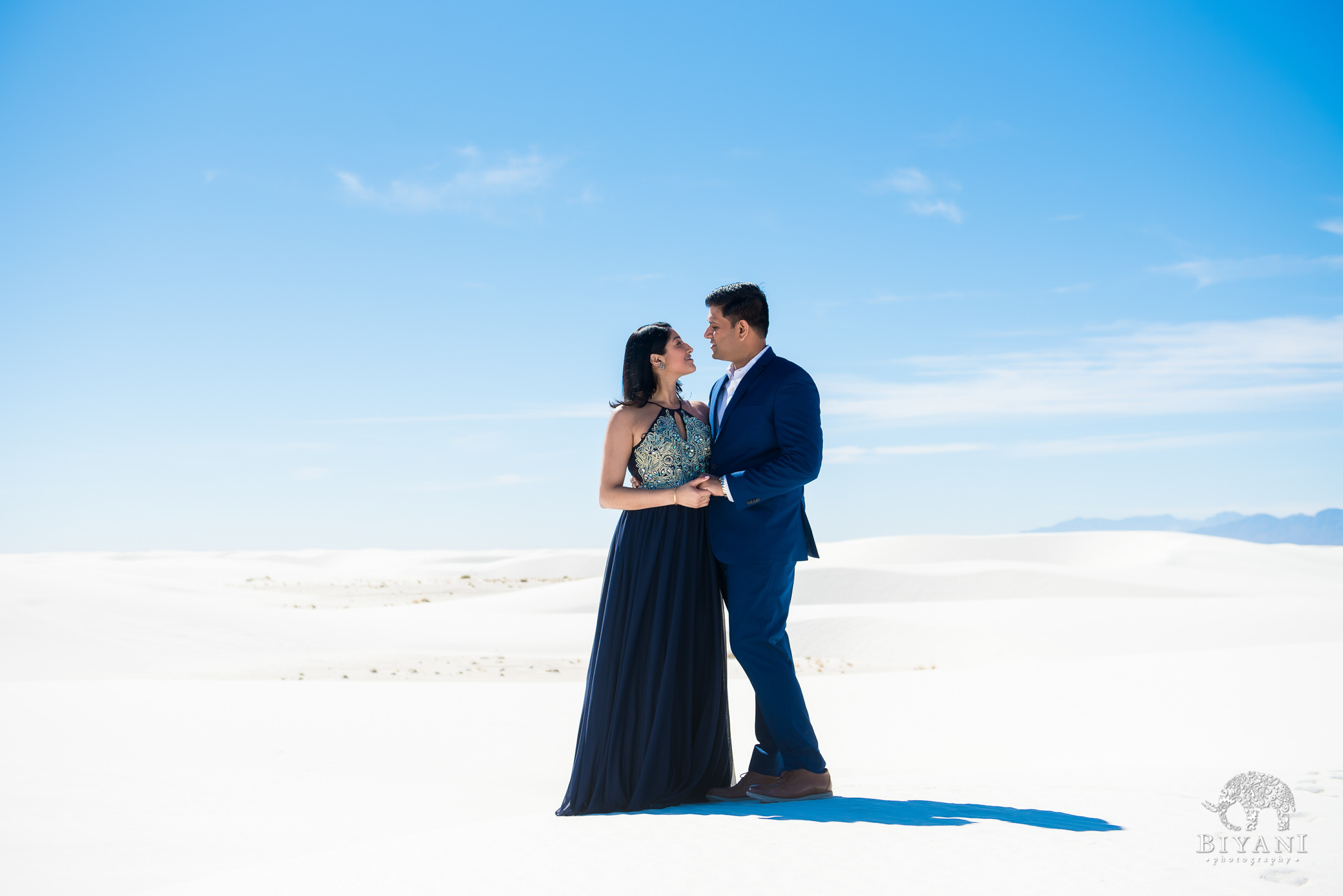 couple holding hands while the wind blows on them on top of a sand dune