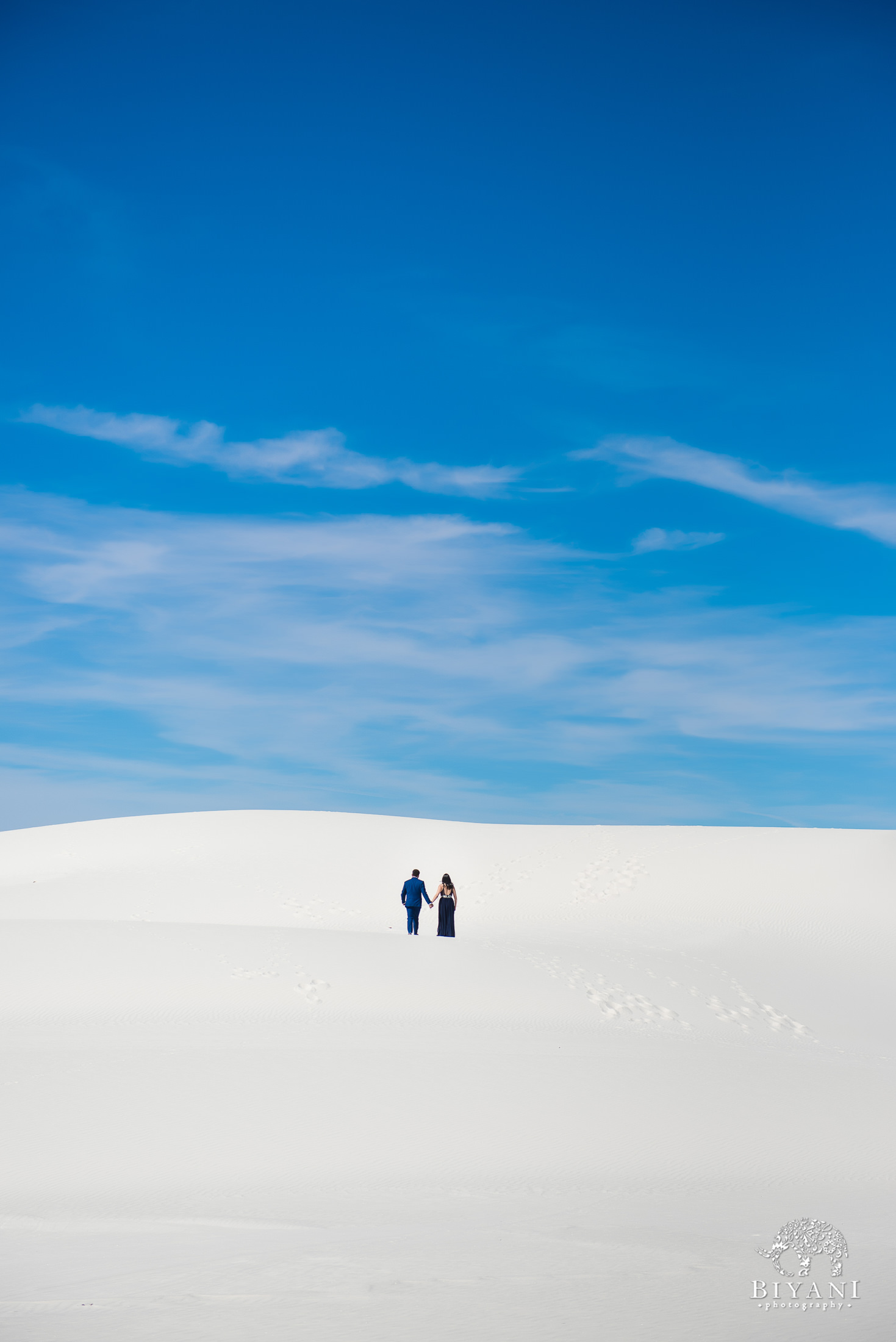 couple photographed from afar walking up a sand dune