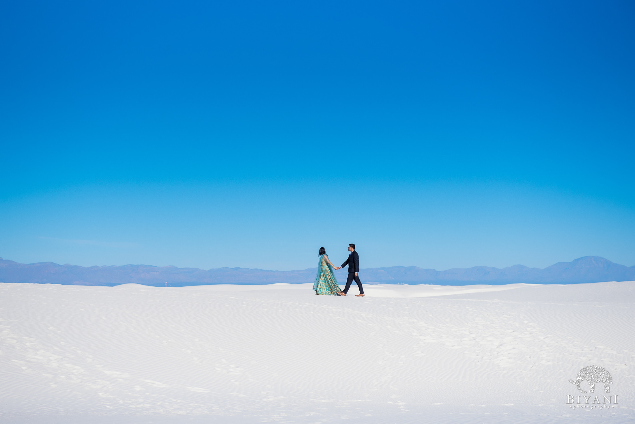 couple walking across sand dunes dressed in their traditional Indian wear