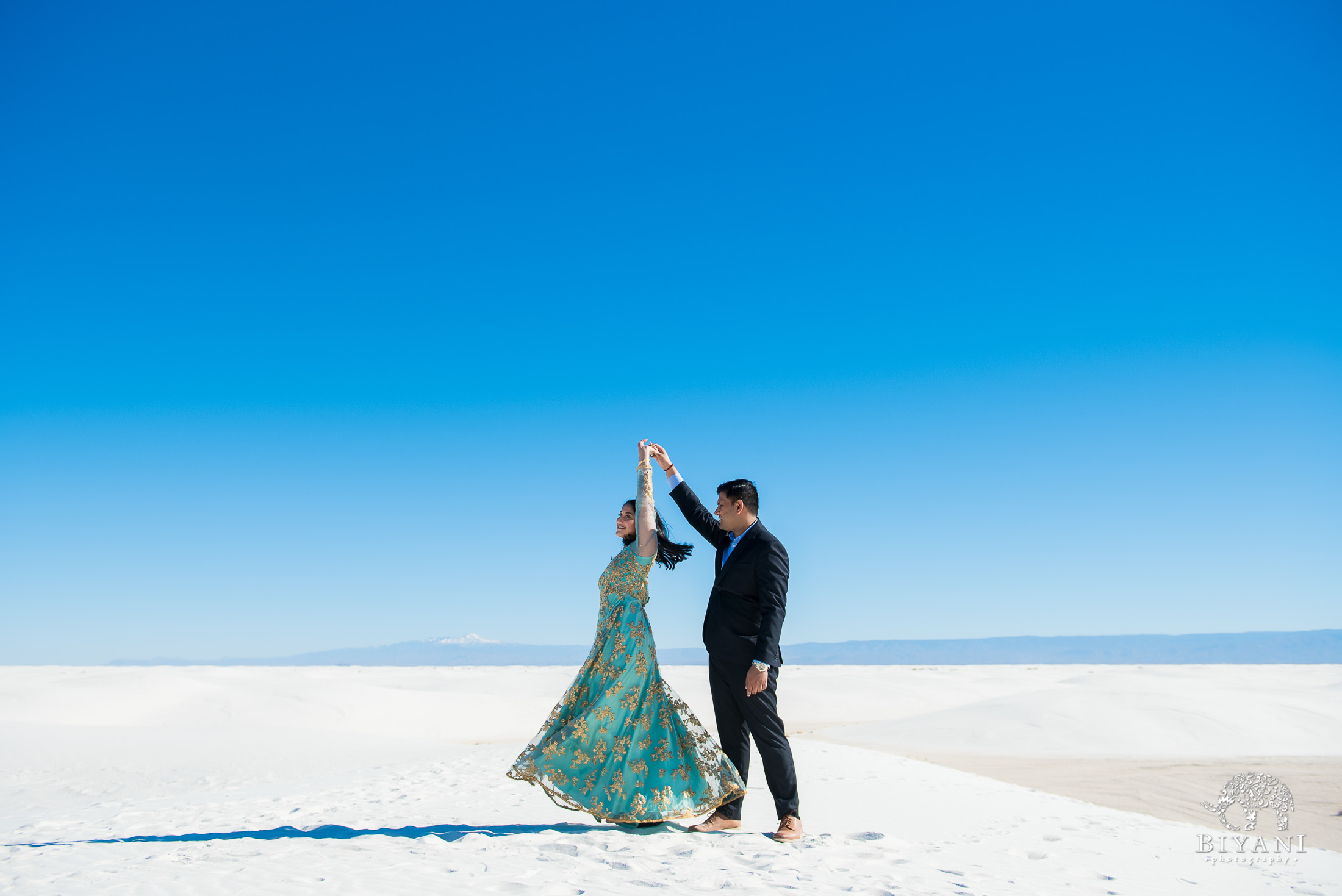 Groom to be twirls bride during sunny day in the sand dunes while dressed in traditional Indian dress