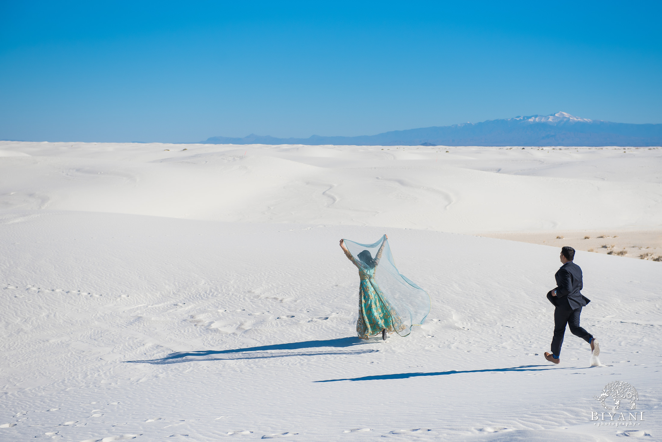 Indian bride to be lets her scarf blow in the wind behind her while standing on white sand