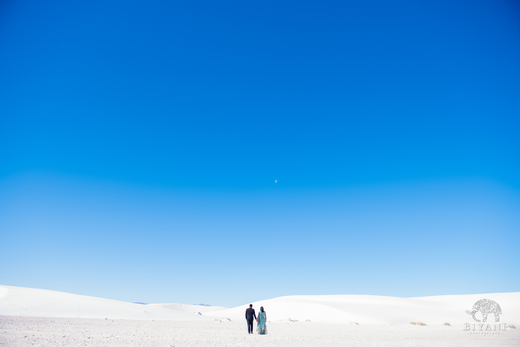 couple walks further into the distance across the white sand dunes